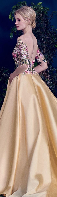 Vestido de fiesta y su peinado recogido moño rubio bajo largo dorado y flores en Cordoba